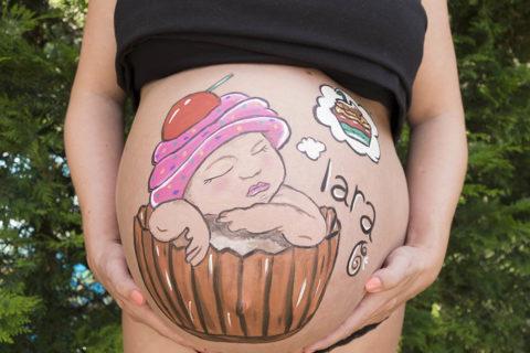 Pintura corporal para embarazada de bebe con dulce para