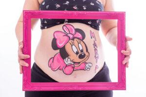foto barriguita pintada con un dibujo de Minnie en tonos rosas