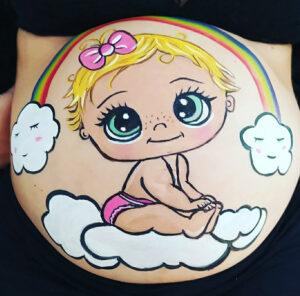 Foto de barriguita pintada en una sesión de baby shower con un diseño de un bebe arcoiris