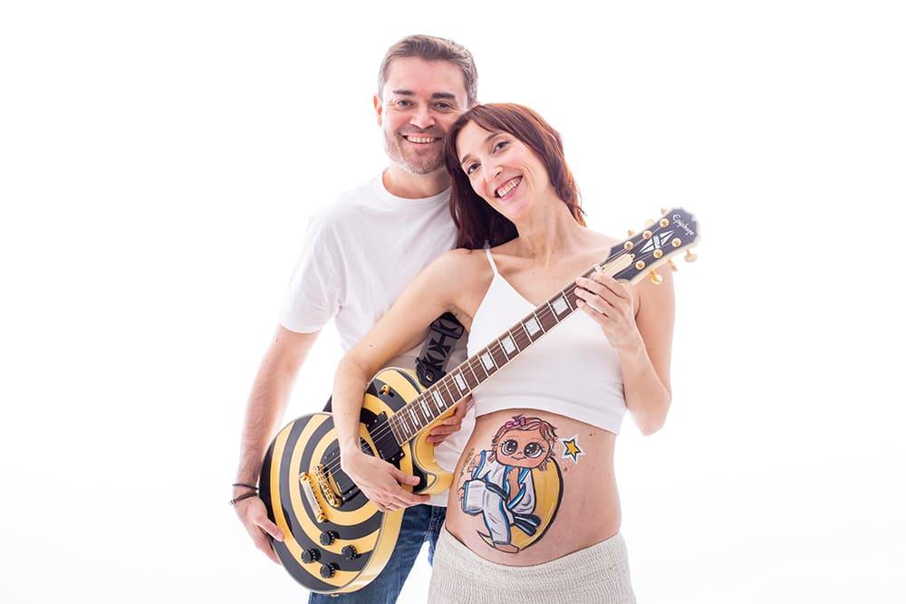 foto de pareja en una sesion de belly painting en estudio con una guitarra