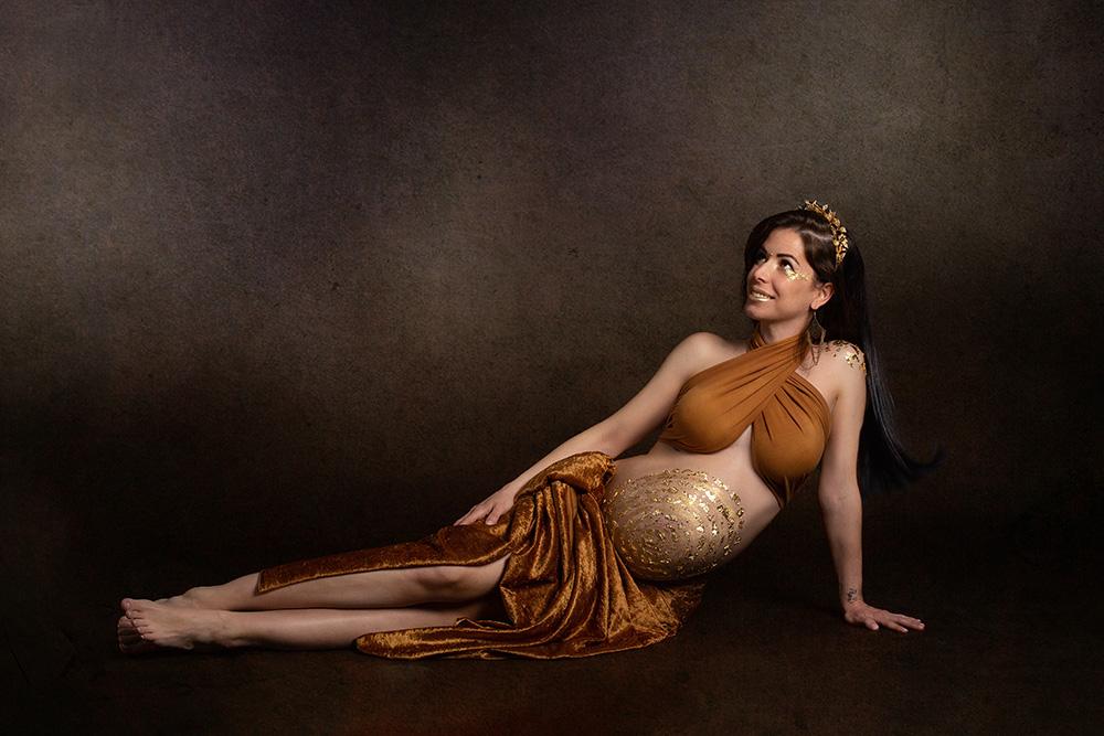 foto de mujer embarazada en una sesion de estudio con maquillaje de body paint con pan de oro en todo el cuerpo y en la cara