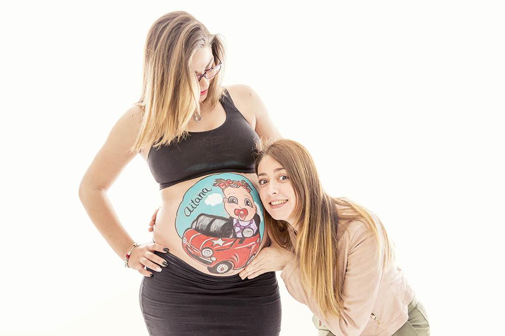 foto de amigas en una baby shower en madrid la embarazada tiene la barriguita pintada con una bebe y un coche