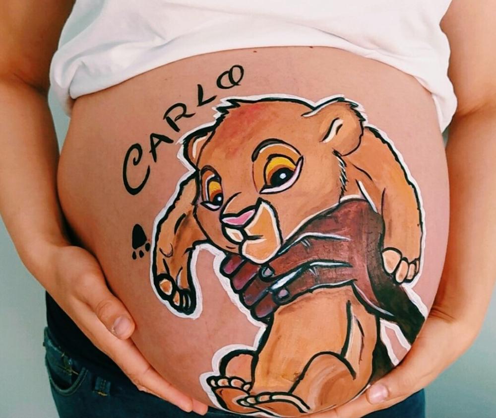 foto de belly painting de una embarazadada con un dibujo de simba en tonos marrones