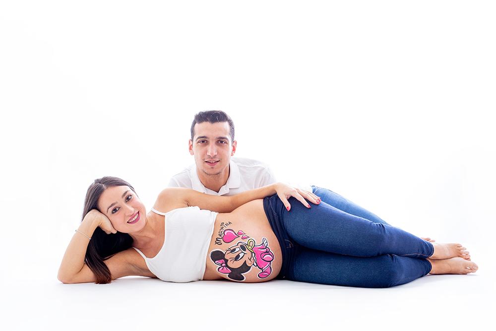 foto de pareja en una sesion de belly painting en estudio en la que pintamos la tripita a la mujer embarazada con un dibujo de minnie mouse