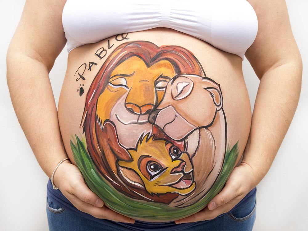 foto de barriguita pintada de una mama con un dibujo del rey leon en tonos anaranjados