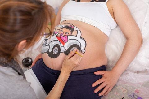 foto de sesion de belly painting en estudio en la que estoy pintando una barriguita con un dibujo de una bebe subida a un taxi